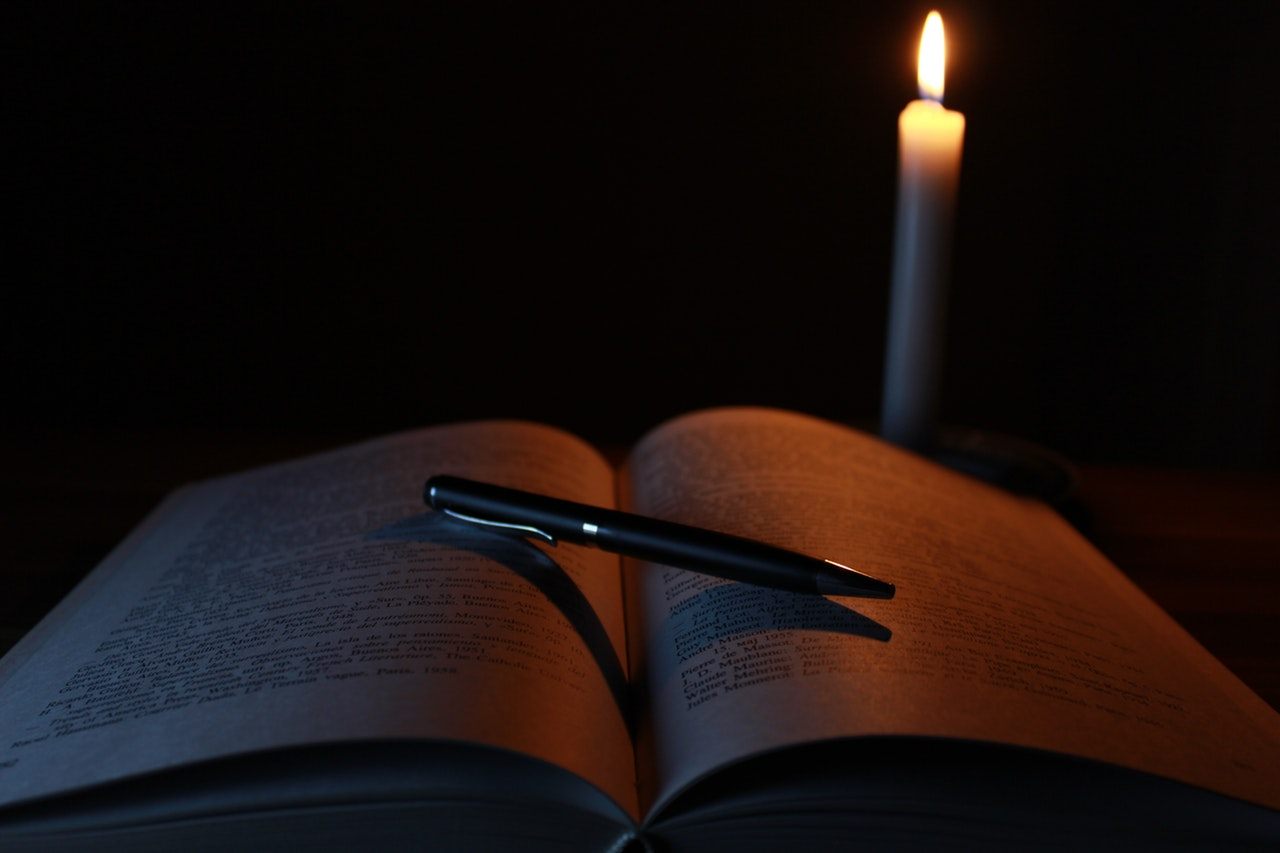 Candle behind book.